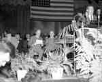 Harry S. Truman listens to a speech