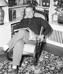 Fred Hartley sitting in a chair with a book