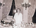 Perle Mesta standing at table in front of decorations