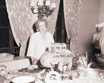 Perle Mesta standing at a table in front of decorations