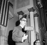 Bill Hickey stands with a giant gavel hand by Ace (Armando) Alagna, 1925-2000