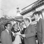 Young visitors hand a book to a NJ legislator