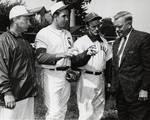 Baseball coach Owen Carroll with three unidentified team members