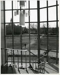 Top of stairwell of the Bishop Dougherty Student Center showing chandelier, encased glass windows, and scenery outside